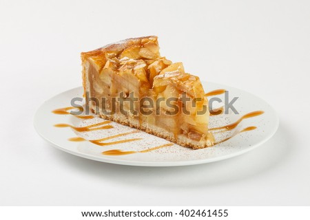 Delicious apple pie (charlotte) with caramel on the plate on white background. Close up side view. #402461455