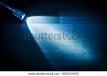 Flashlight and a beam of light in darkness. A modern led lamp with bright projection on dark wood table. Surface with copy space. Royalty-Free Stock Photo #402659605