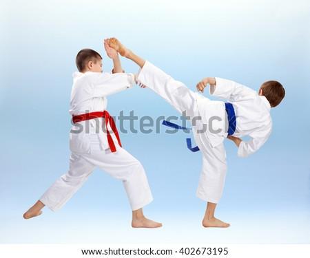 High kick and block are training boys in karategi #402673195