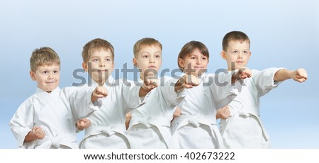 Five children hit a punch on a light background #402673222