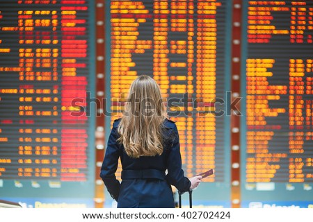 Young woman in international airport looking at the flight information board, holding passport in her hand, checking her flight Royalty-Free Stock Photo #402702424