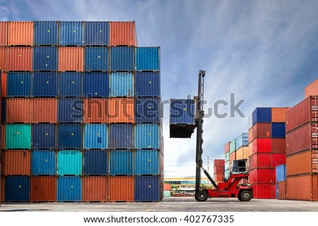 Crane lifting up container in yard Royalty-Free Stock Photo #402767335