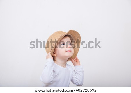 Little girl with hat on a white background. #402920692