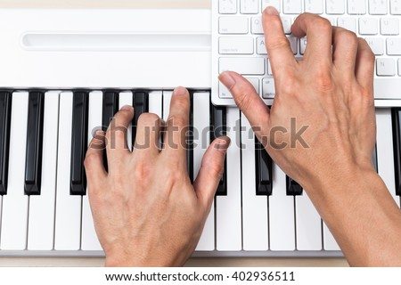 professional asian composer hands making songs on piano keys & computer for music production concept #402936511
