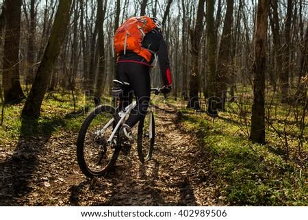 Mountain biker riding on bike in springforest landscape.  #402989506