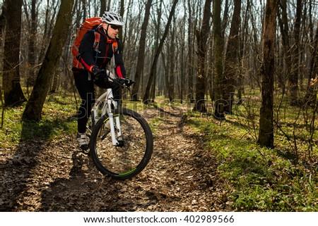 Mountain biker riding on bike in springforest landscape.  #402989566