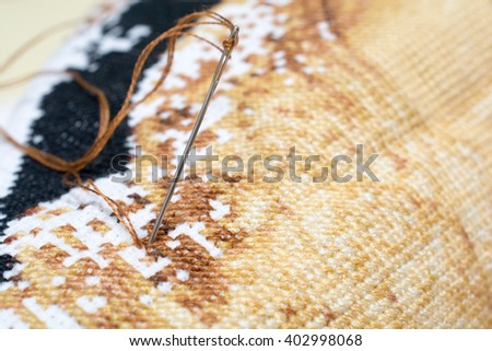 Closeup of needle put into cross stitch embroidery #402998068