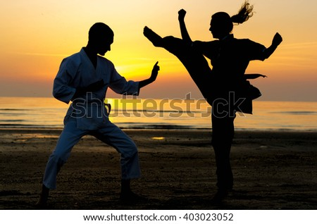 Artial marts fight between master and his pupil at the beach during the sunrise - silhouette - concept about people, lifestyle and sport Royalty-Free Stock Photo #403023052