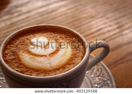 Cappuccino cup close up in a woody table #403129588