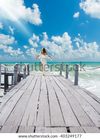 Woman walking on the wooden deck at the tropical resort #403249177