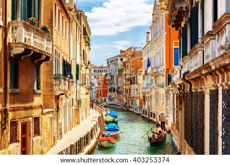 View of the Rio Marin Canal with boats and gondolas from the Ponte de la Bergami in Venice, Italy. Venice is a popular tourist destination of Europe. Royalty-Free Stock Photo #403253374