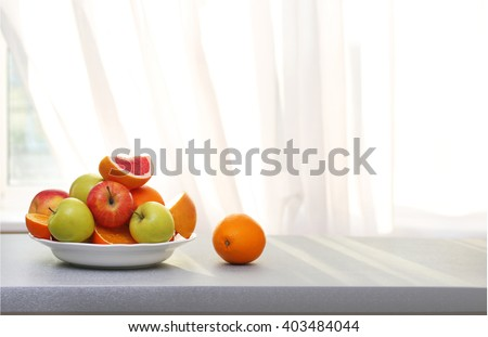 Plate of ripe fruits on a table #403484044