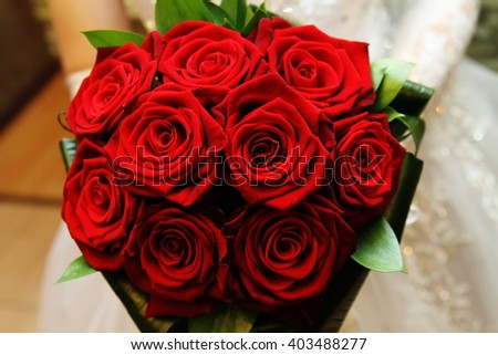Bride holding her wedding bouquet of red roses #403488277