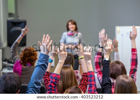 Diverse Group of Students in Conference Room raising Arms up actively participating in Seminar Teachers Body on background Royalty-Free Stock Photo #403523212