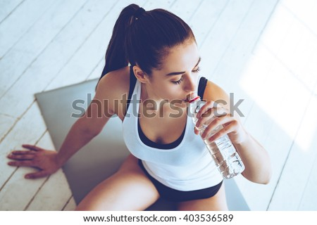 Sip of fresh water after great workout. Top view of beautiful young woman drinking water while sitting on exercise mat at gym  Royalty-Free Stock Photo #403536589