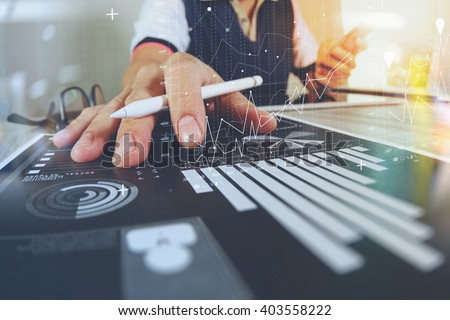 business documents on office table with smart phone and digital tablet and graph finance with social network diagram and man working in the background Royalty-Free Stock Photo #403558222
