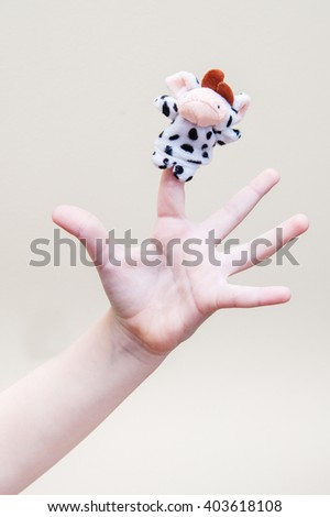 Children's palm with a toy cow on the index finger #403618108
