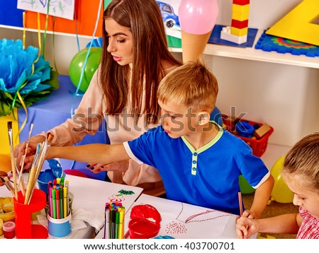 Happy children and teacher draw paints in the kids' club. #403700701