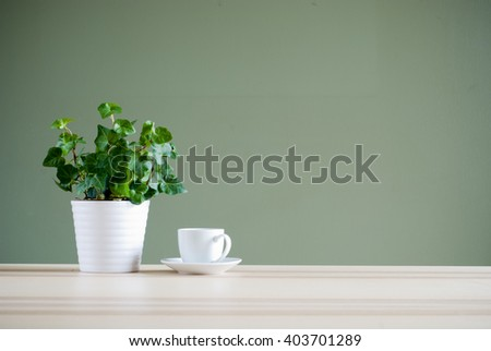 green plant and coffee cup on desk #403701289