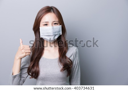 A Woman wears a mask and thumb up, illness, asian beauty,gray background #403734631