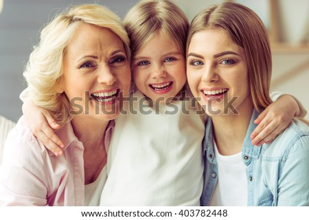 Portrait of three generations of happy beautiful women looking at camera, hugging and smiling #403782448