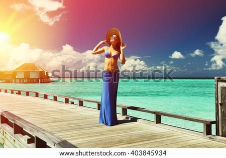 Woman on a tropical beach jetty at Maldives #403845934