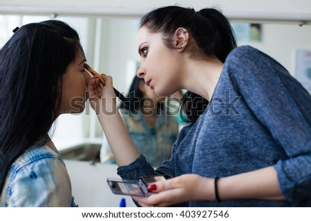 Young female  make-up artist working in her studio,  applying makeup on a client, preparing model to the beauty photo session #403927546