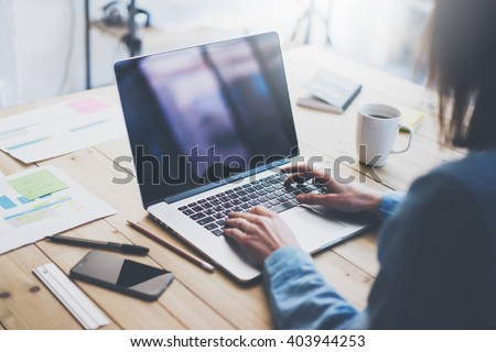 Working process photo.Woman working wood table with new business project.Typing contemporary laptop, reflections screen. Modern smartphone table.Horizontal.Film effect. Blurred background #403944253
