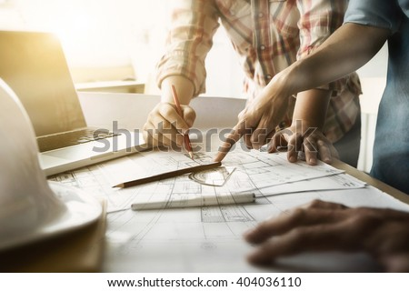 Image of engineer meeting for architectural project. working with partner and engineering tools on workplace vintage tone. Royalty-Free Stock Photo #404036110