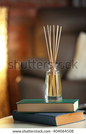 Handmade reed freshener with books on white table in living room, close up #404064508