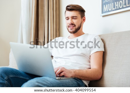 Handsome man using laptop computer on the couch at home #404099554