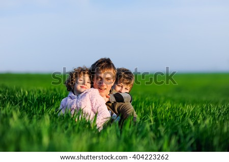 Happy boys and girls lying on a green grass. Group of happy children, kids, friends, brother and sister outdoors on summer nature. Young family smiling, spending time together, have fun outside.  #404223262