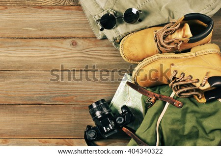 Travel accessories set on wooden background: old hiking leather boots, pants, backpack, map, vintage film camera and sunglasses. Top view point. Royalty-Free Stock Photo #404340322