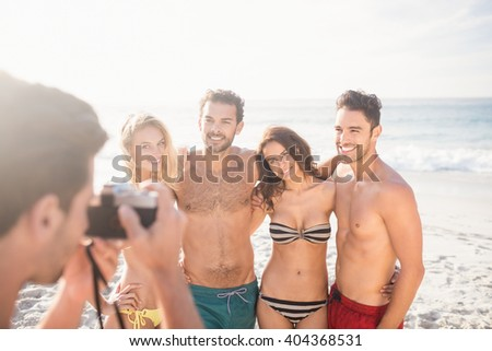 Man taking picture of his friends on the beach