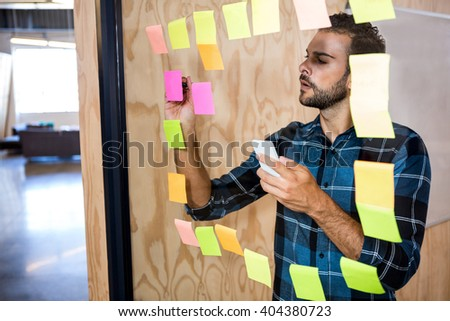 Man using mobile phone while writing on sticky notes in office #404380723