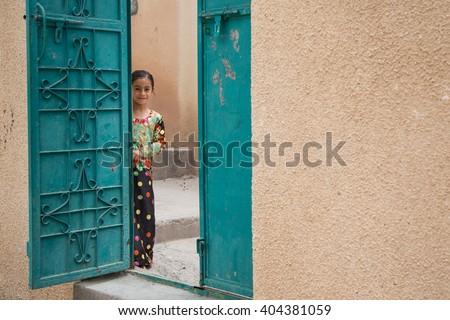 JABAL AL AKHDAR, OMAN - CIRCA APRIL 2016: little Omani girl is looking from behind the gate door #404381059