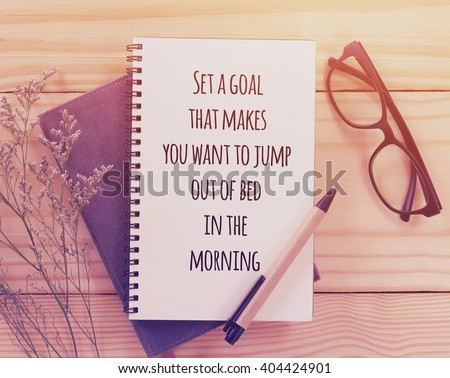 Inspirational motivating quote on notebook with vintage filter
