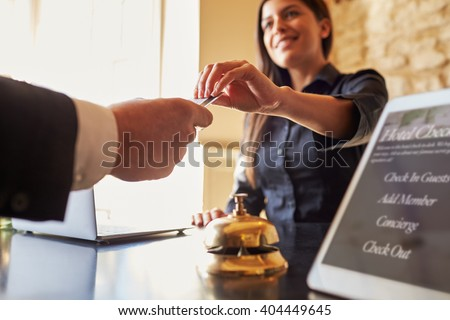 Guest takes room key card at check-in desk of hotel, close up Royalty-Free Stock Photo #404449645