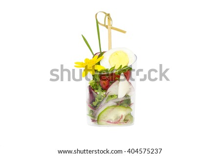 mini canapes in plastic cups decorated with edible flowers #404575237