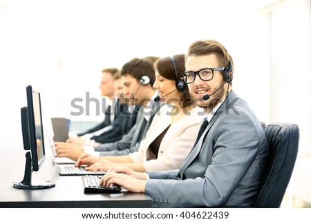 Attractive young man working in a call center with his colleagues #404622439