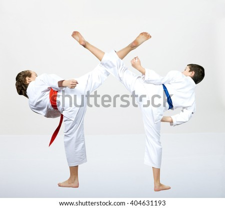 A guy with a blue belt and a girl with a red belt makes a high kick #404631193