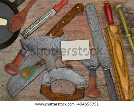 vintage bakery shop tools and utensils over stained wooden table, blank business card for your text