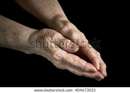 Old woman clasped in her hands on a black background #404673025