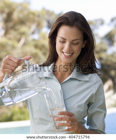 Woman pouring a glass of water #404715796