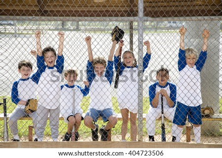 Little league baseball team cheering behind wire fence Royalty-Free Stock Photo #404723506
