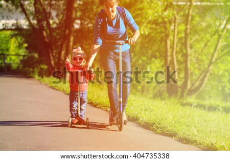 mother and little daughter on scooters in the city #404735338