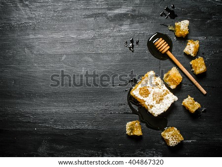 Honey background. Natural honey comb and a wooden spoon . On black rustic table. #404867320