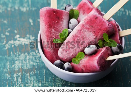 Homemade blueberry ice cream or popsicles decorated green mint leaves on teal rustic table, frozen fruit juice, vintage style. Royalty-Free Stock Photo #404923819