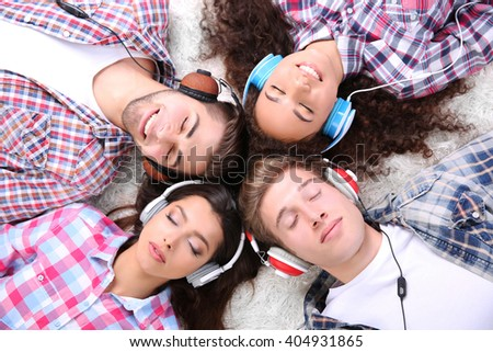 Two teenager couples listening to music with headphones on a carpet #404931865