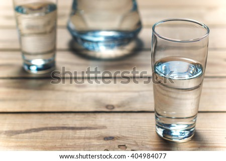 Glasses of water on a wooden table. Selective focus. Shallow DOF #404984077
